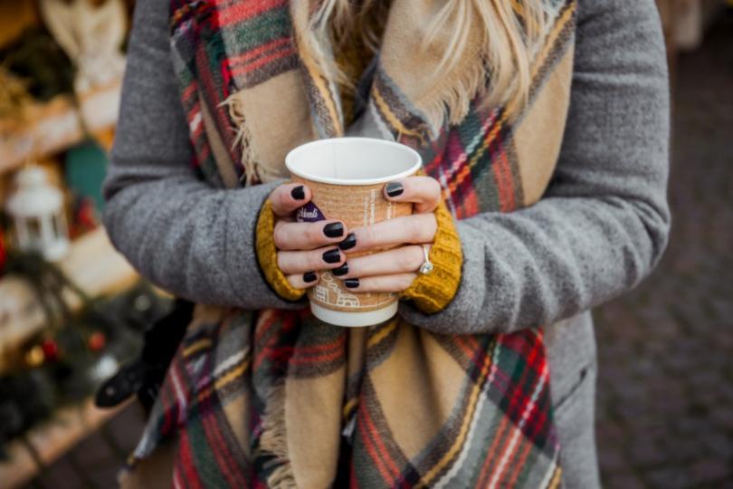 Frau mit Kaffeebecher in der Hand
